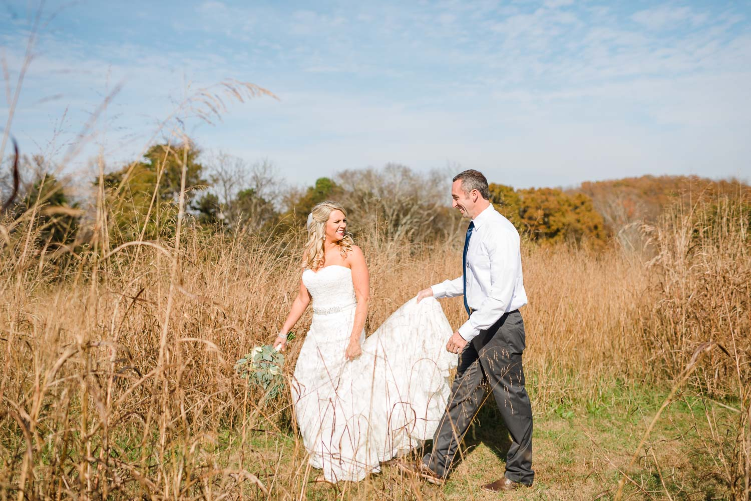 wedding couple walking through tall brown grass on a sunny november day in TN