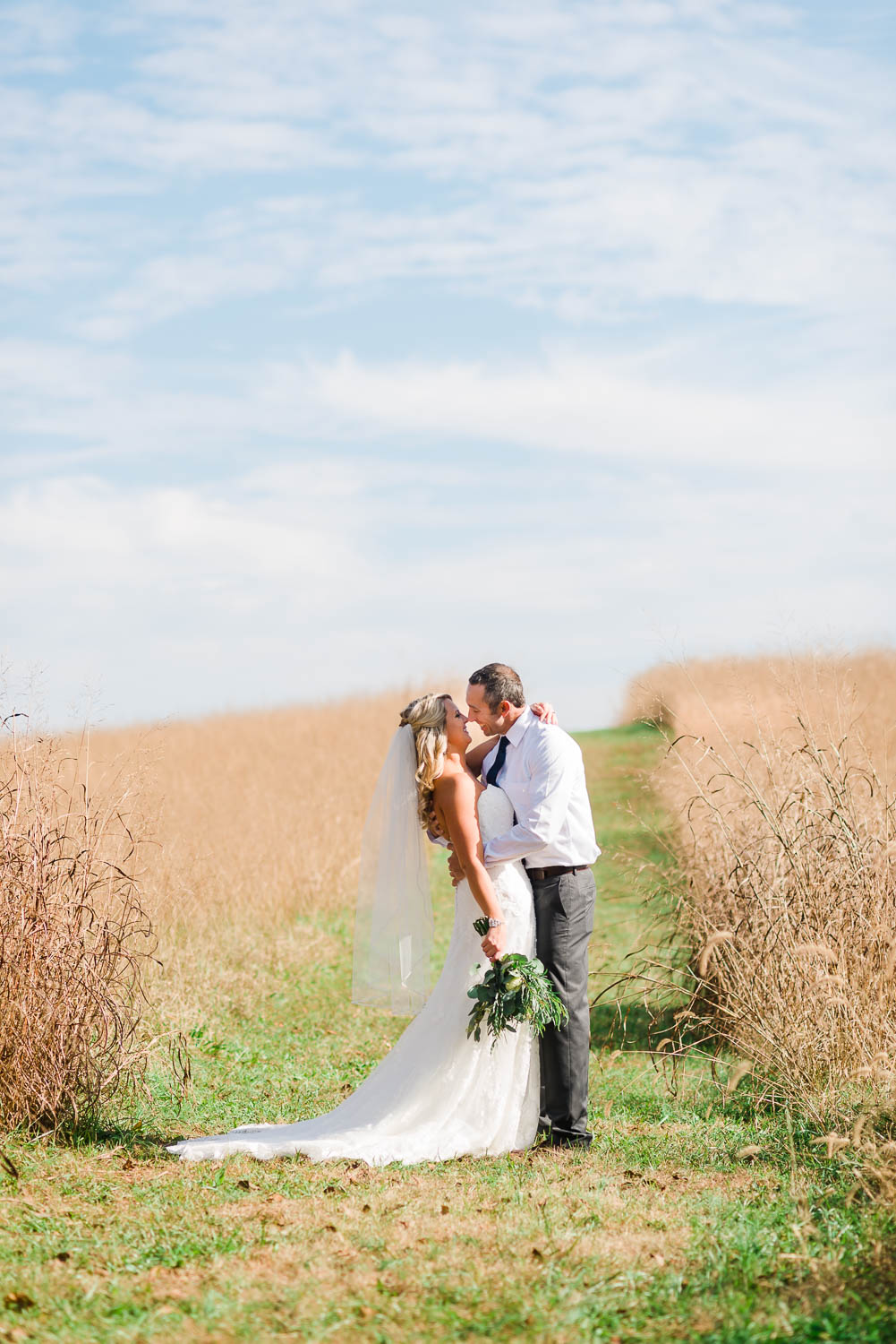 bride and groom in the middle of long grassy path through a field at their barn wedding