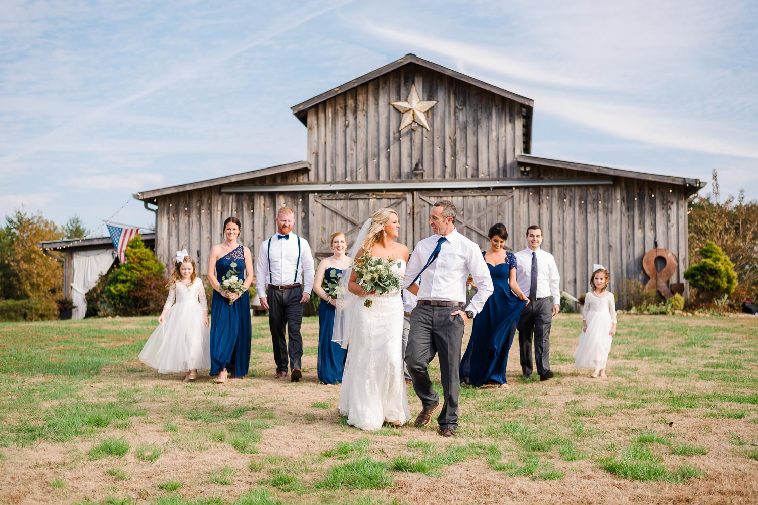 navy and white wedding party in front of rustic Tennessee barn venue
