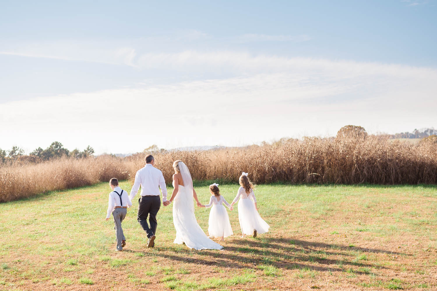 family walking off into the sessing sun in wedding attire at the Barn at Drewia Hill in East Tennessee