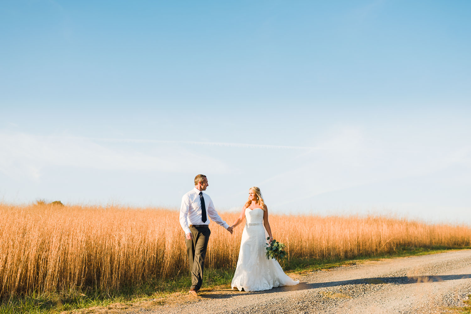 wedding couple walking at edge of brown field and big blue sky in the background in Tennessee.