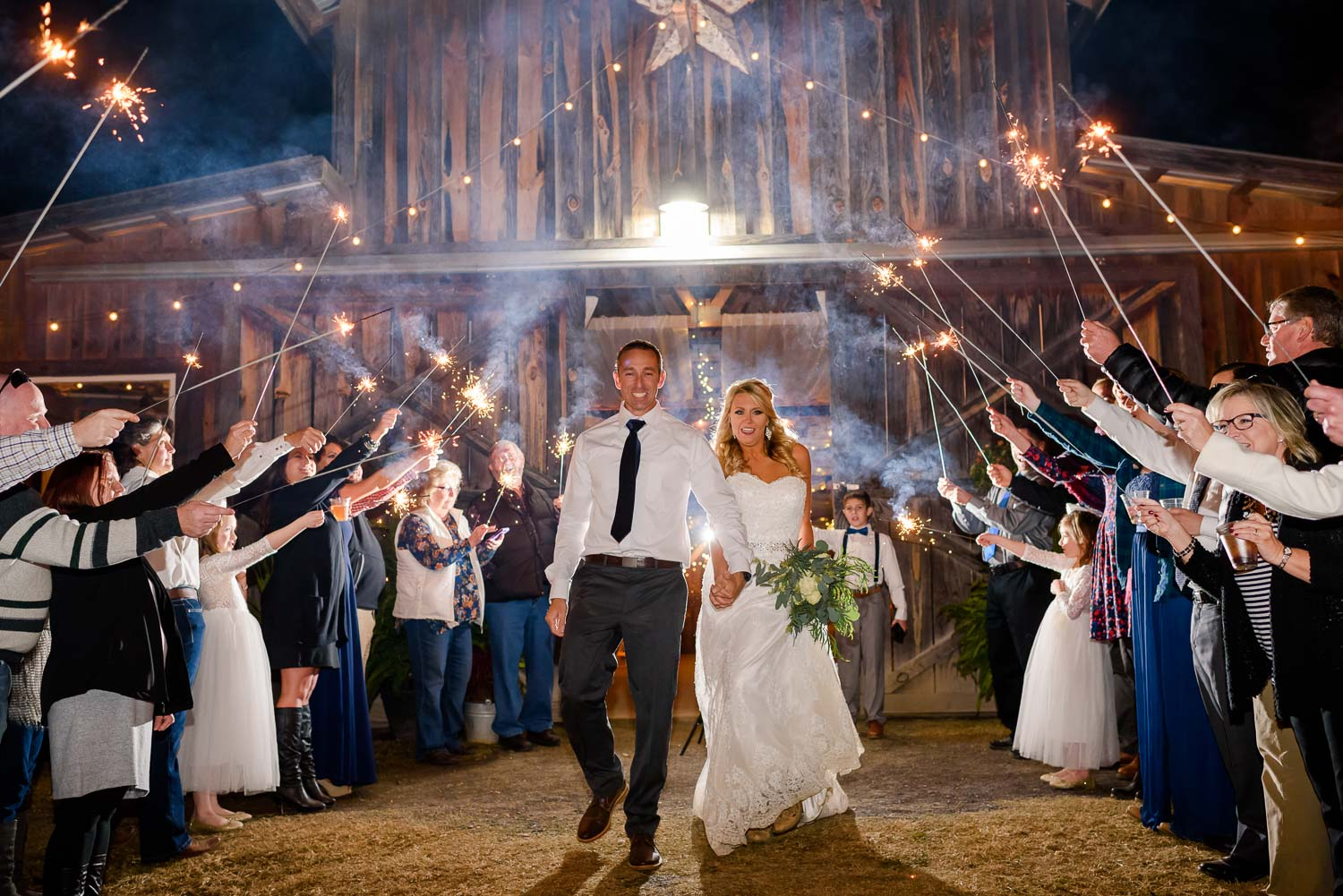 bride and groom running through sparklers in front of the Barn at Drewia Hill