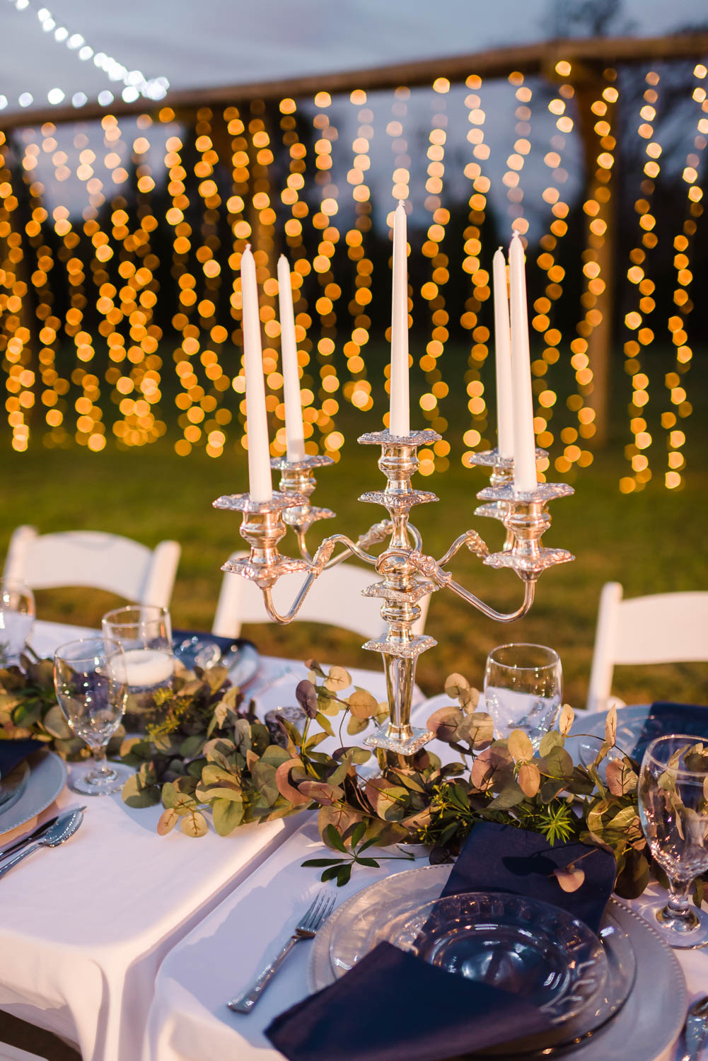 silver candlestick holder with white candles at outdoor reception