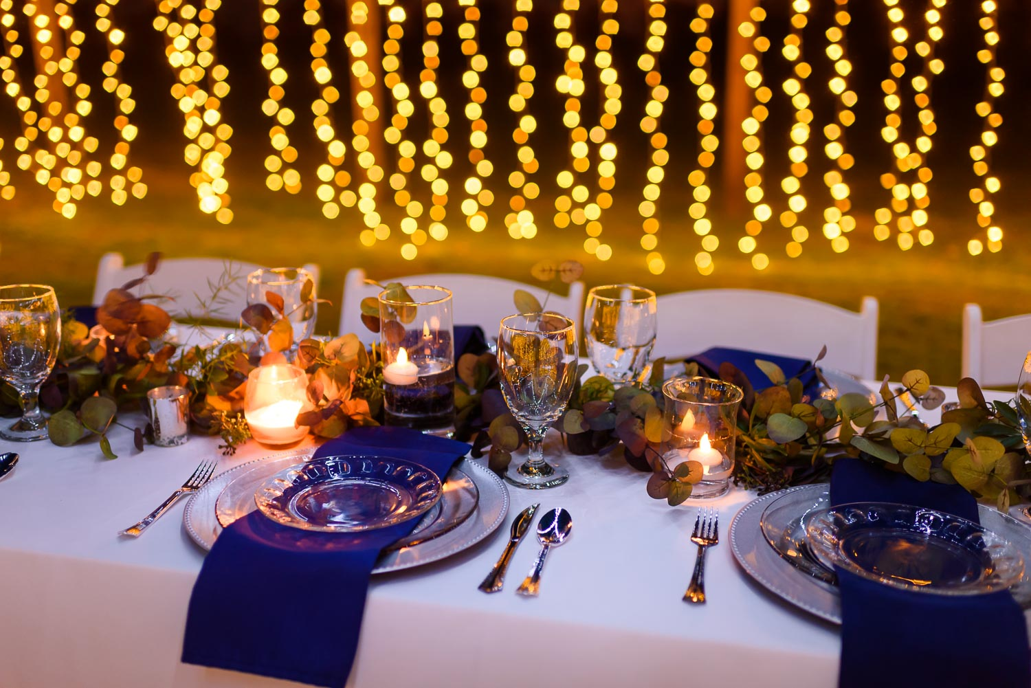 Stunning outdoor candlelight reception in royal blue and warm candle light