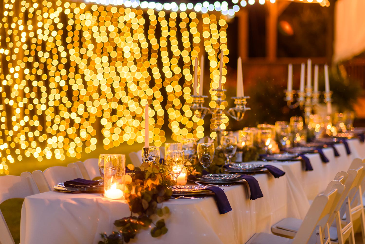 candle lit outside wedding reception with millions of twinkly christmas lights in the background