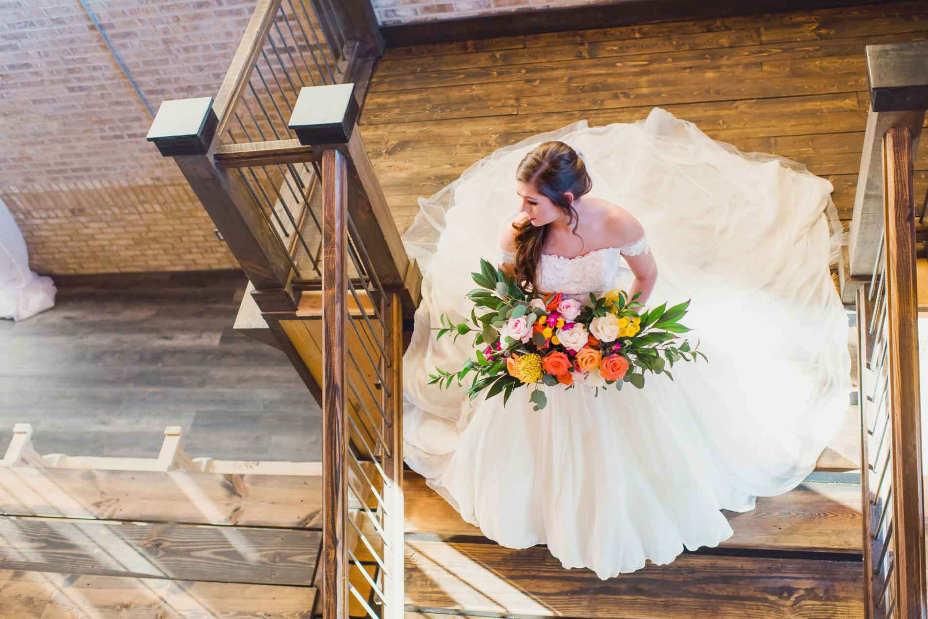 Bride walking down stair case with large bouquet of flowers
