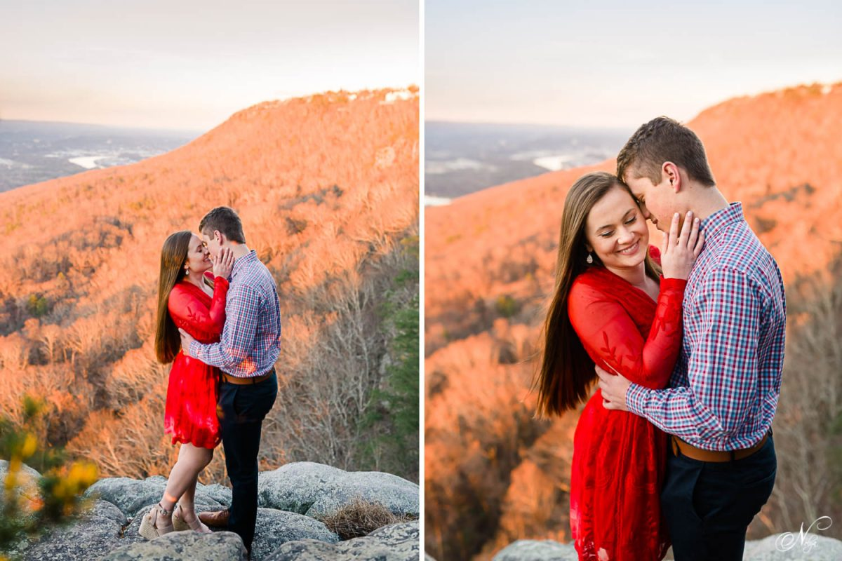engaged couple standding on rocks with orange sunset light covering bare winter trees in the background