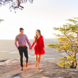 girl in red lace dress and guy in navy pants walking on rock at sunset rock with golden glowing light behind them