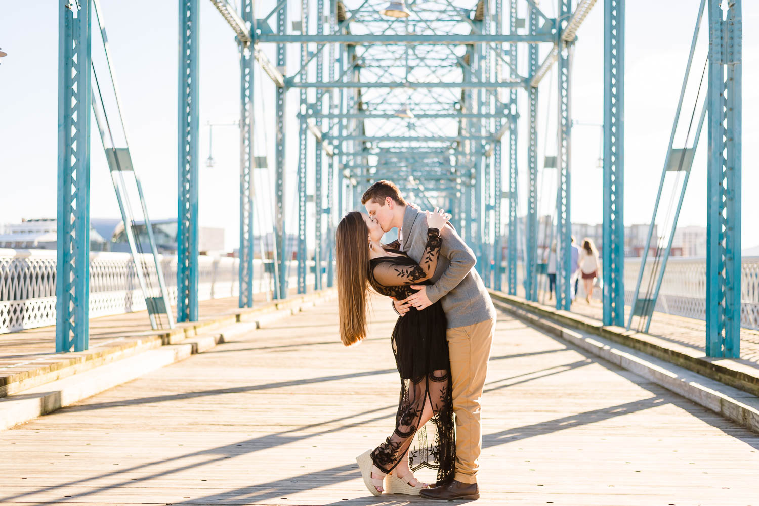 guy dipping his fiance back for a kiss in the middle of the blue walnut st bridge in Chattanooga