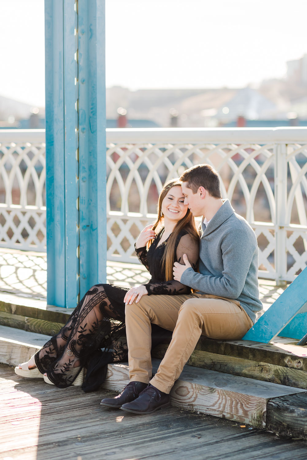 engaged couple sitting on Walnut st bridge enjoying the sunny january day