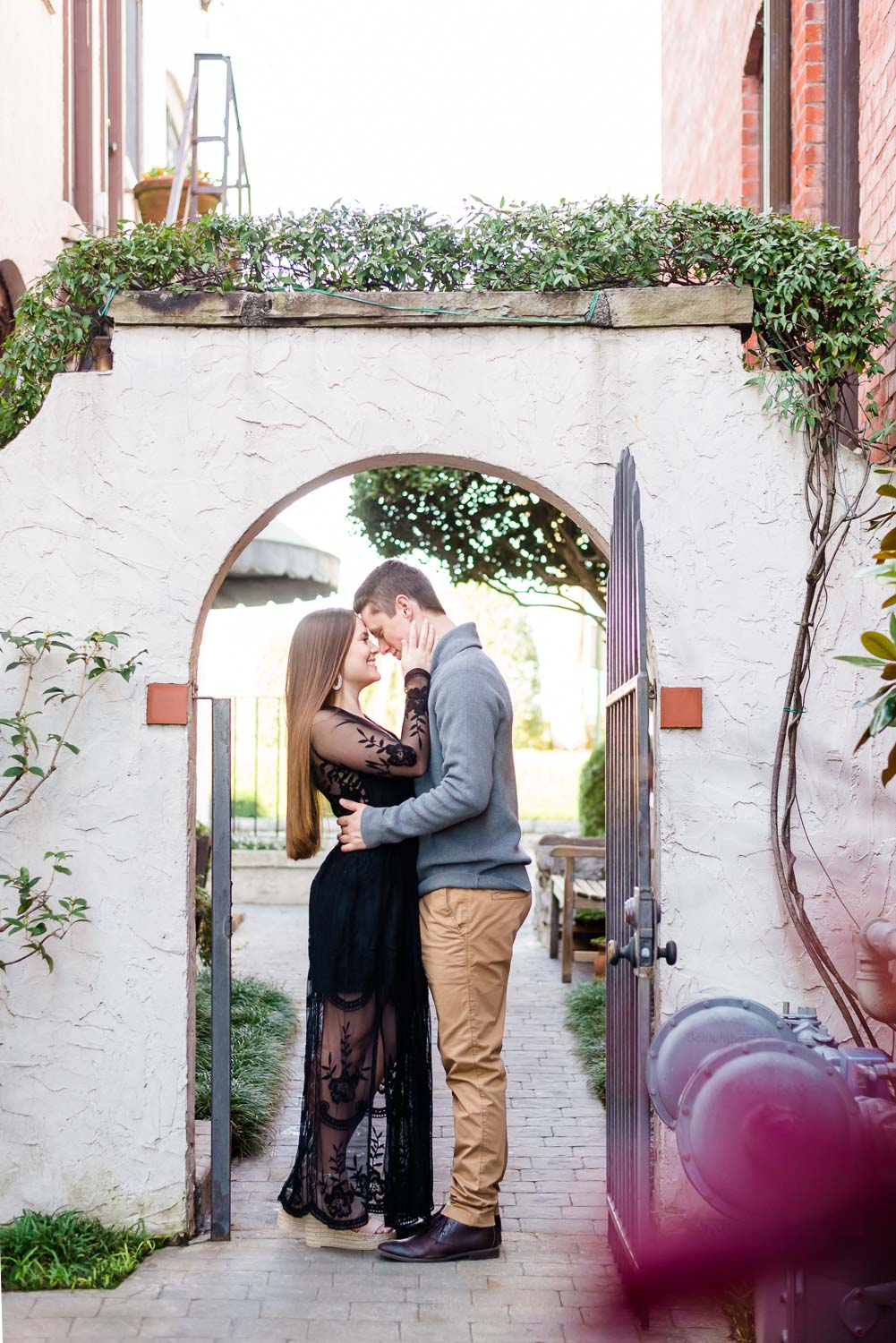 couple at Bluff view Arts district under the white vine covered archway