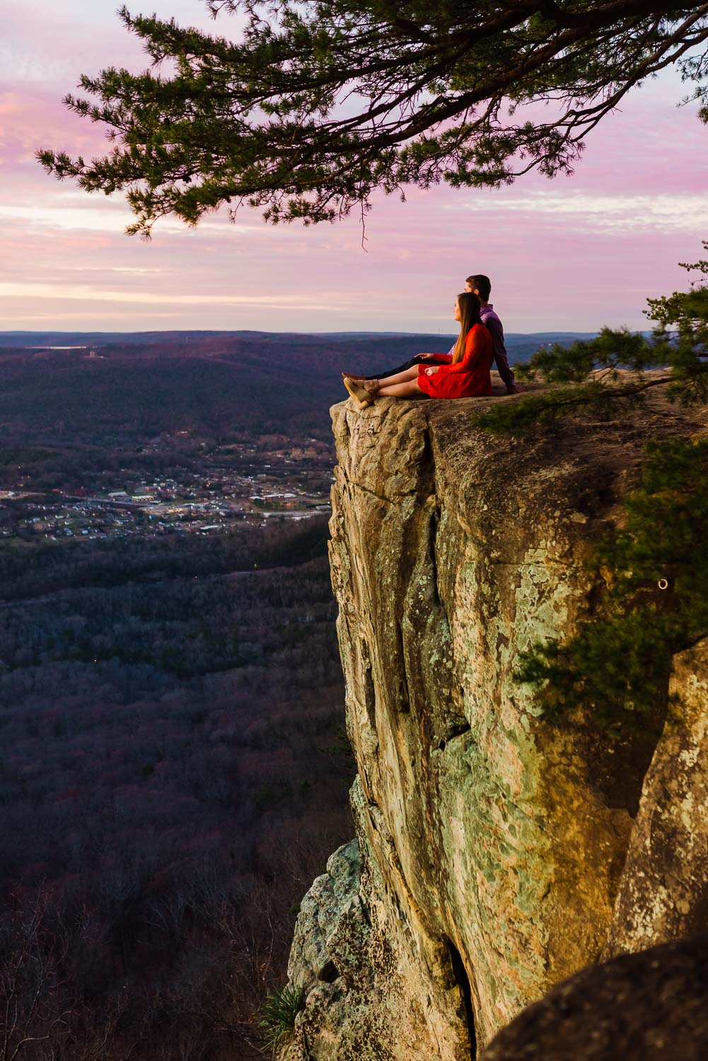 couple sitting on the rock outcropping at Sunset Rock at dusk in Chattanooga