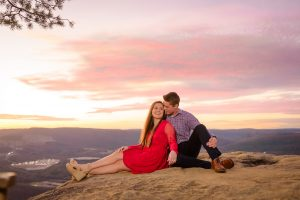 girl in red dress and guy in navy and plaid sitting on rock with glowing pink sky in the background