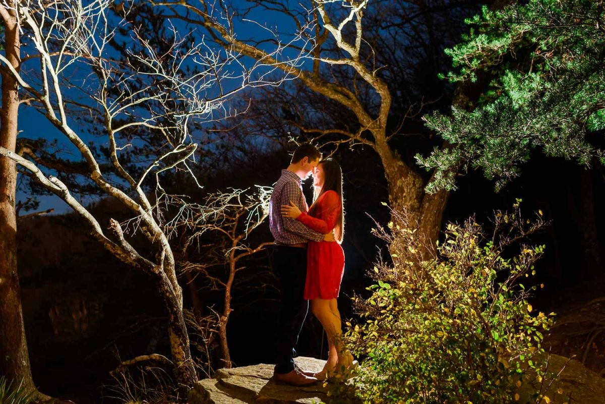 engaged couple outside at night under the trees on the trail at sunset rock in Chattanooga