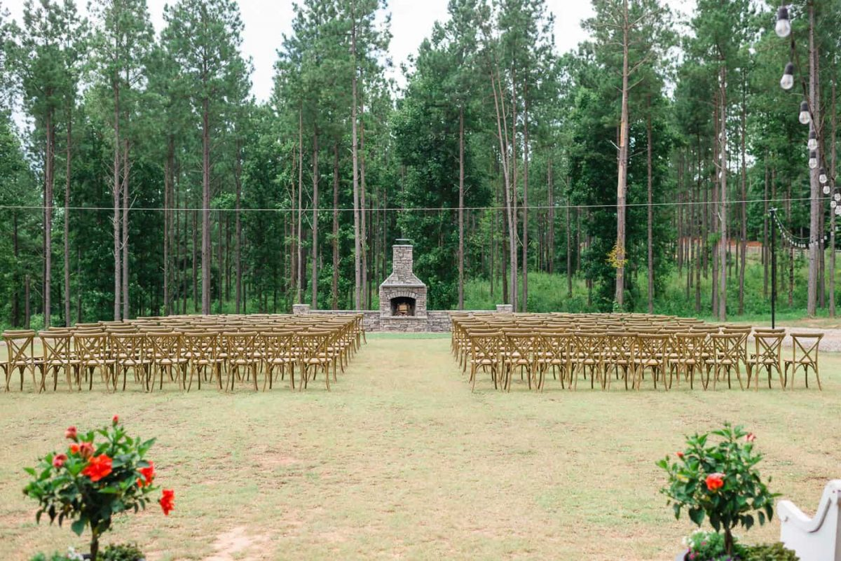 outdoor wedding ceremony with wood crossed backed chairs and pine trees in the background