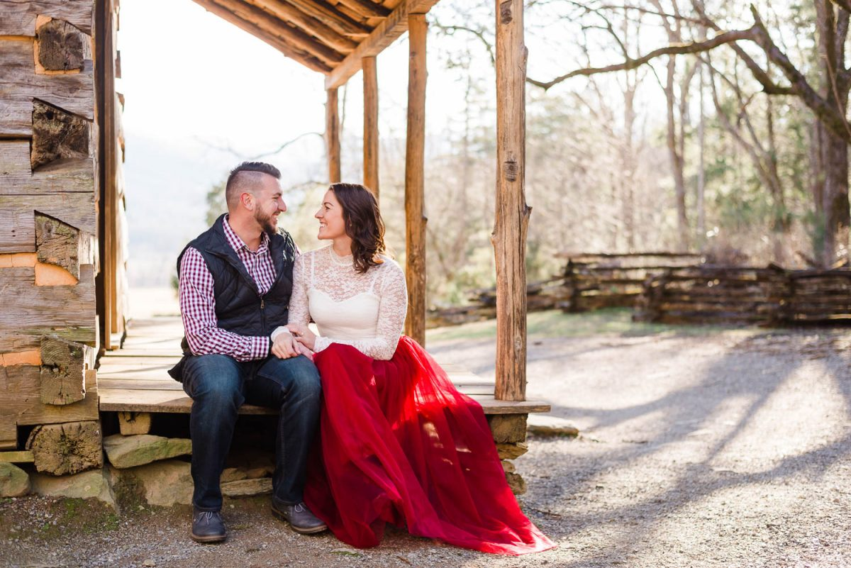 couple sitting on porch of historic cabin in cades cove TN in January