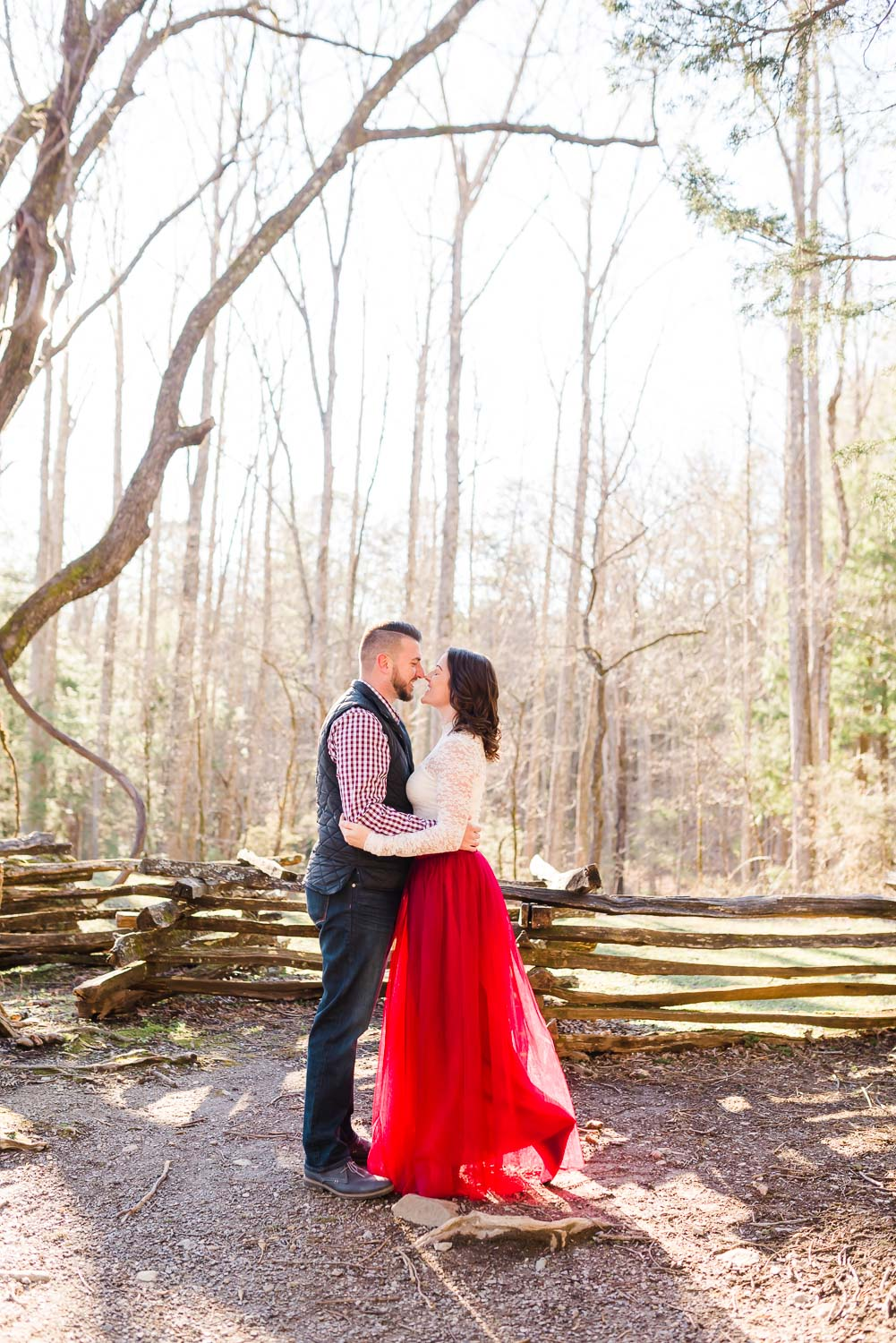 engagement photos of couple in red and navy outside in the mountains near Knoxville