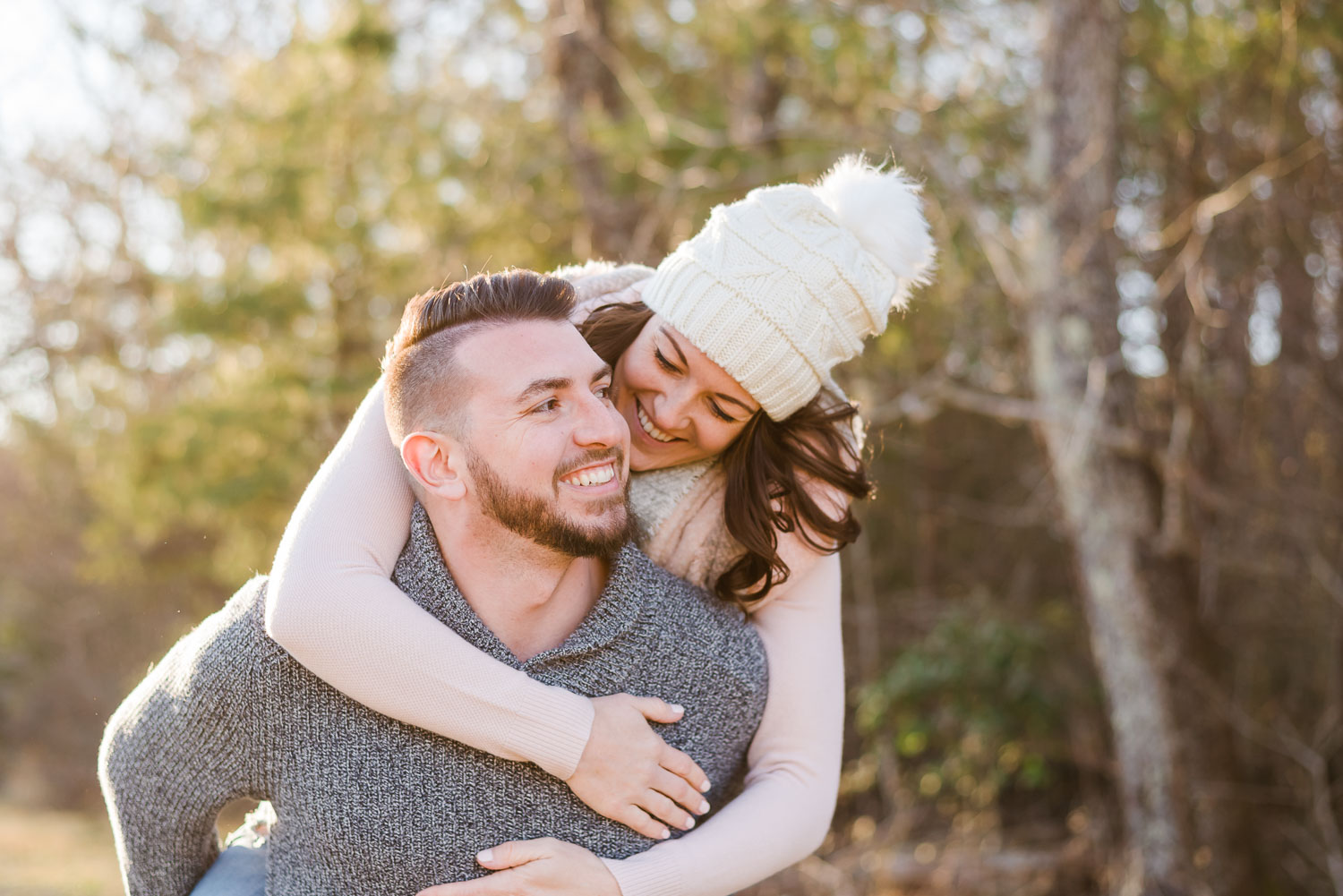 laughing girl reaching around to hug her future husband in january