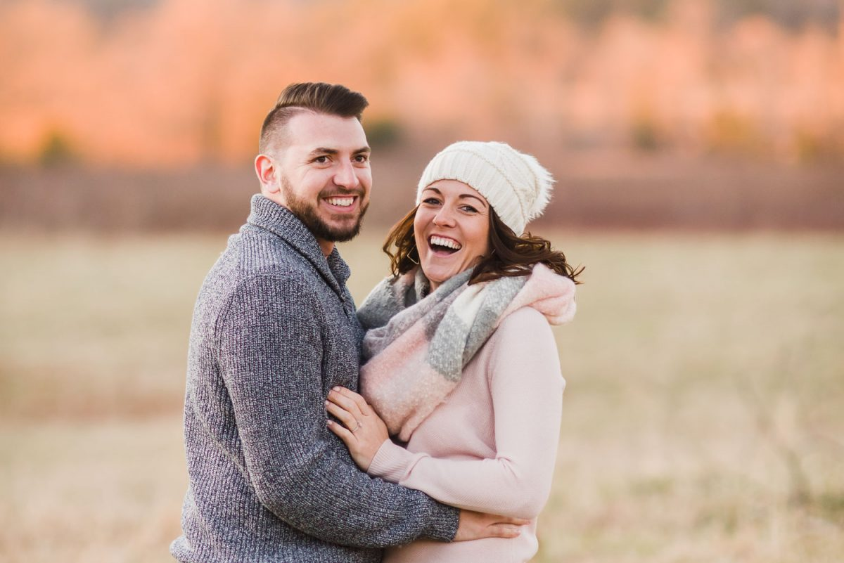 two people outside laughing in the winter in Tennessee during fun engagement photos wearing sweaters