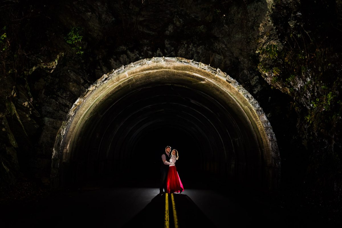 engaged couple standing in the middle of the road at entrance to a tunnel in Tn at night