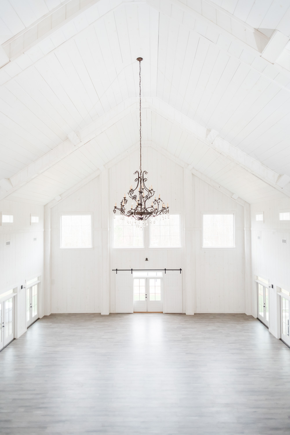 interior of Circle B Events with it's white walls and white ceiling and leage chandelier