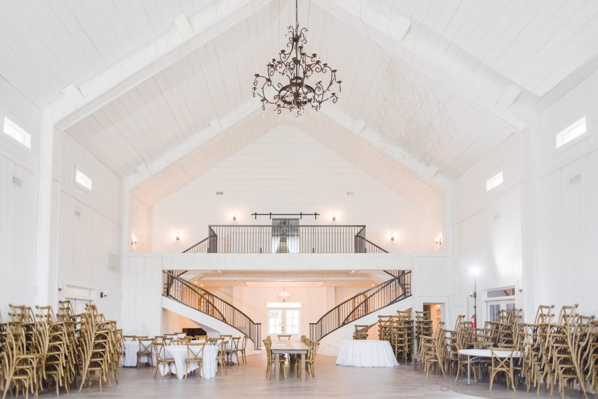 Huge white interior of Circle B events with double curved stair cases and large chandelier