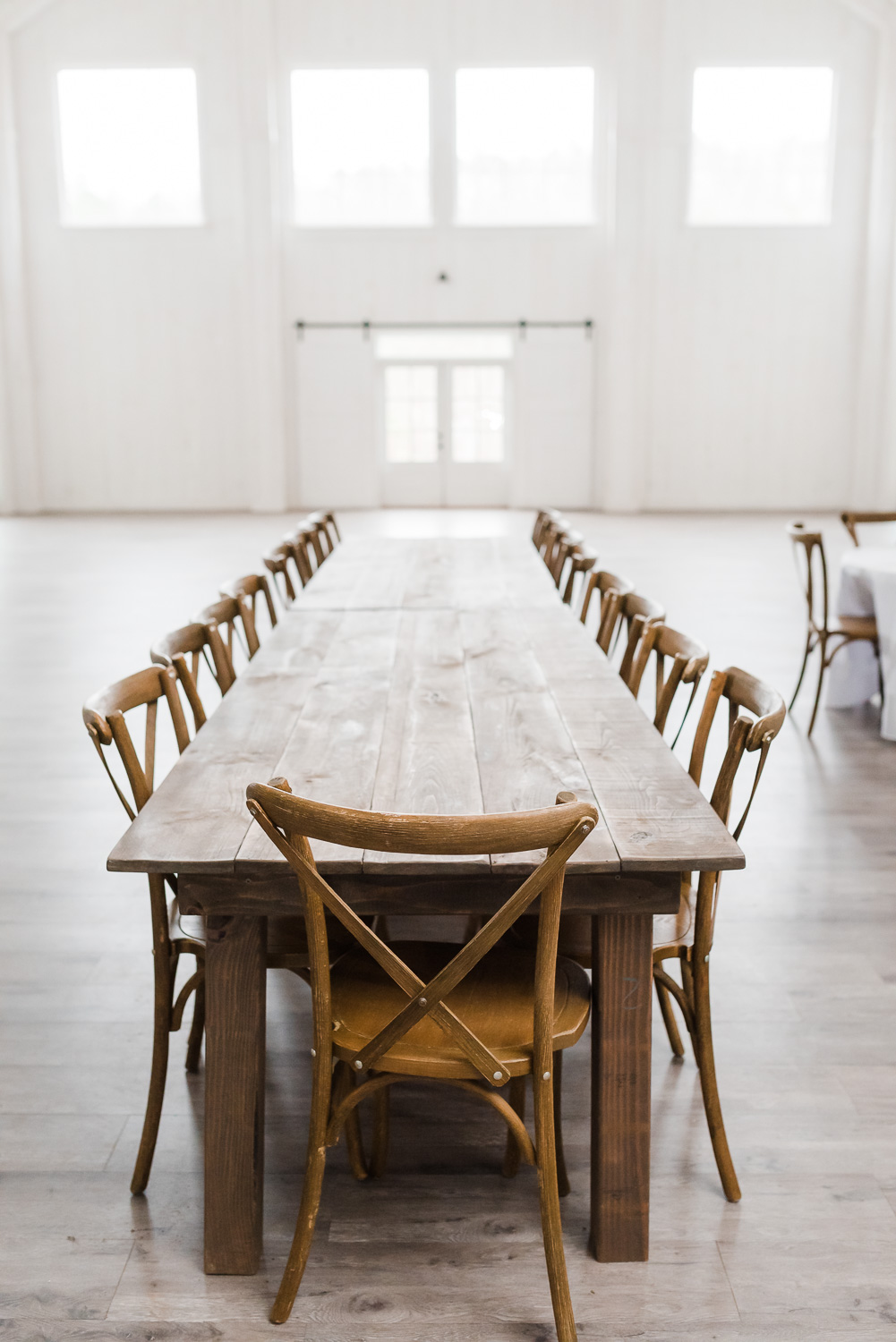 Cross backed chairs at wooden farm table in white room