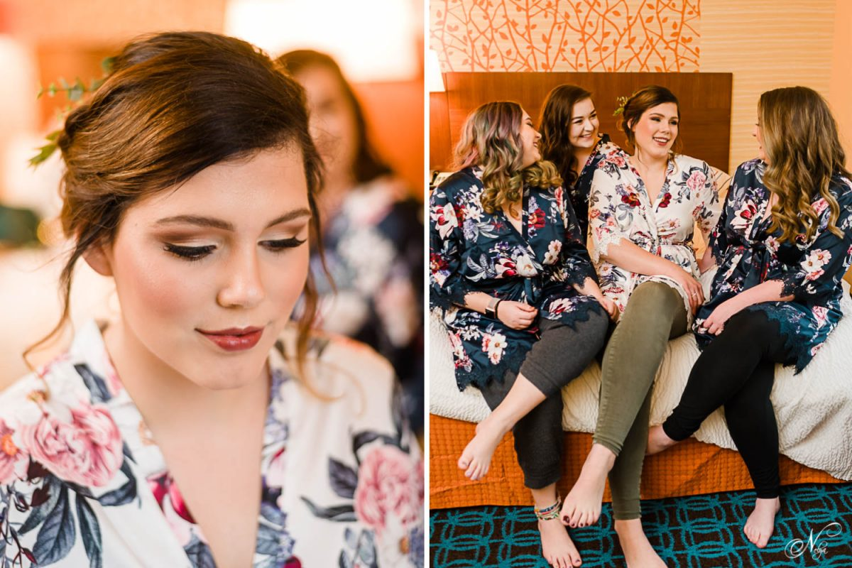 girl in floral robe with her makeup freshly done. And bridesmaids sitting on a bed with the bride laughing and talking.