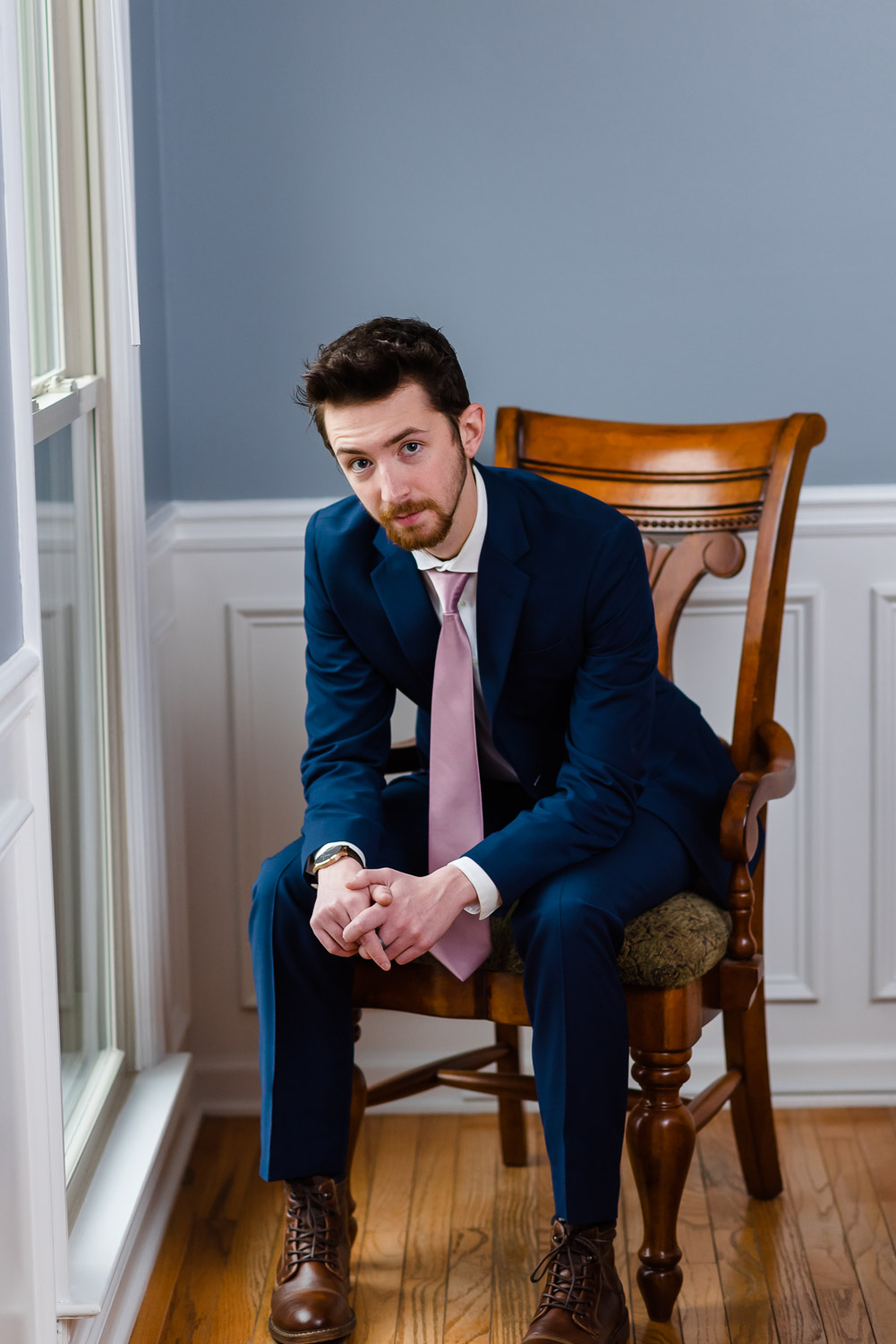 groom in a navy blue suit and dusty rose colored tie.
