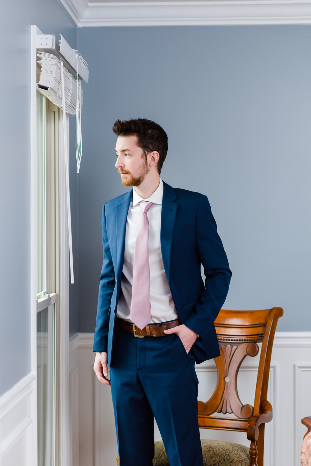 groom in blue suit looking out a window
