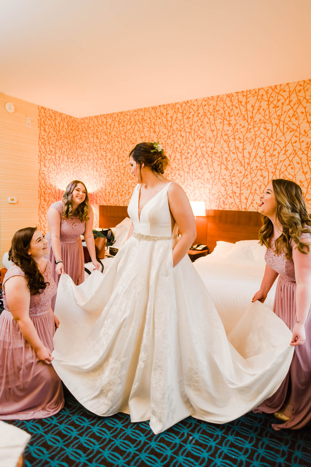 bridesmaids helping bride with her dress.