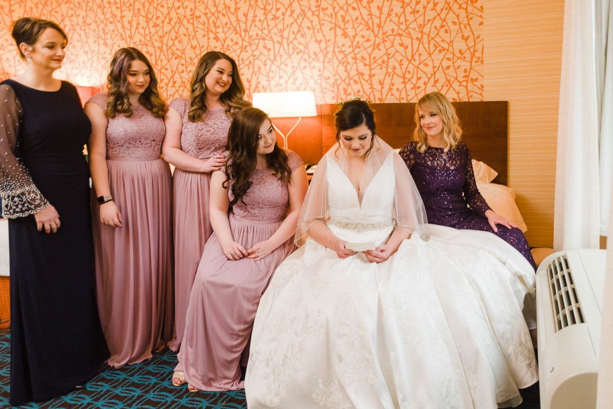 all the girls in the wedding party gathered around the bride in a hotel room.