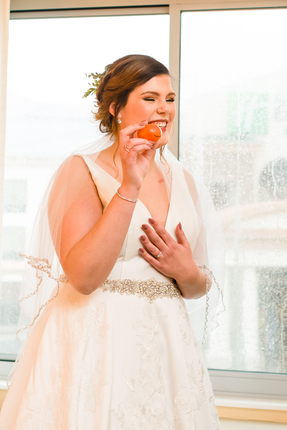 bride laughing holding up a gift.