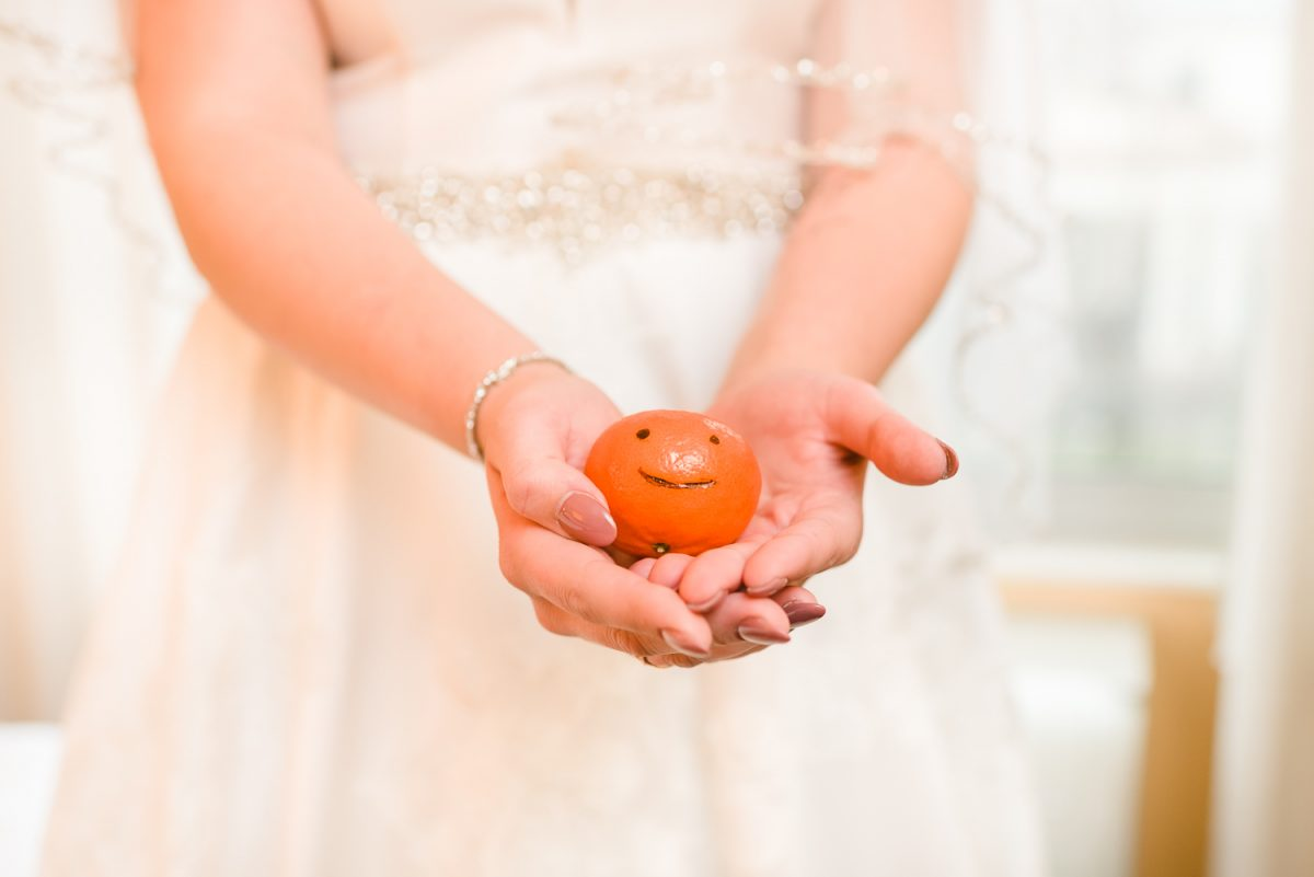 hands holding an orange with a smiley face drawn on it.