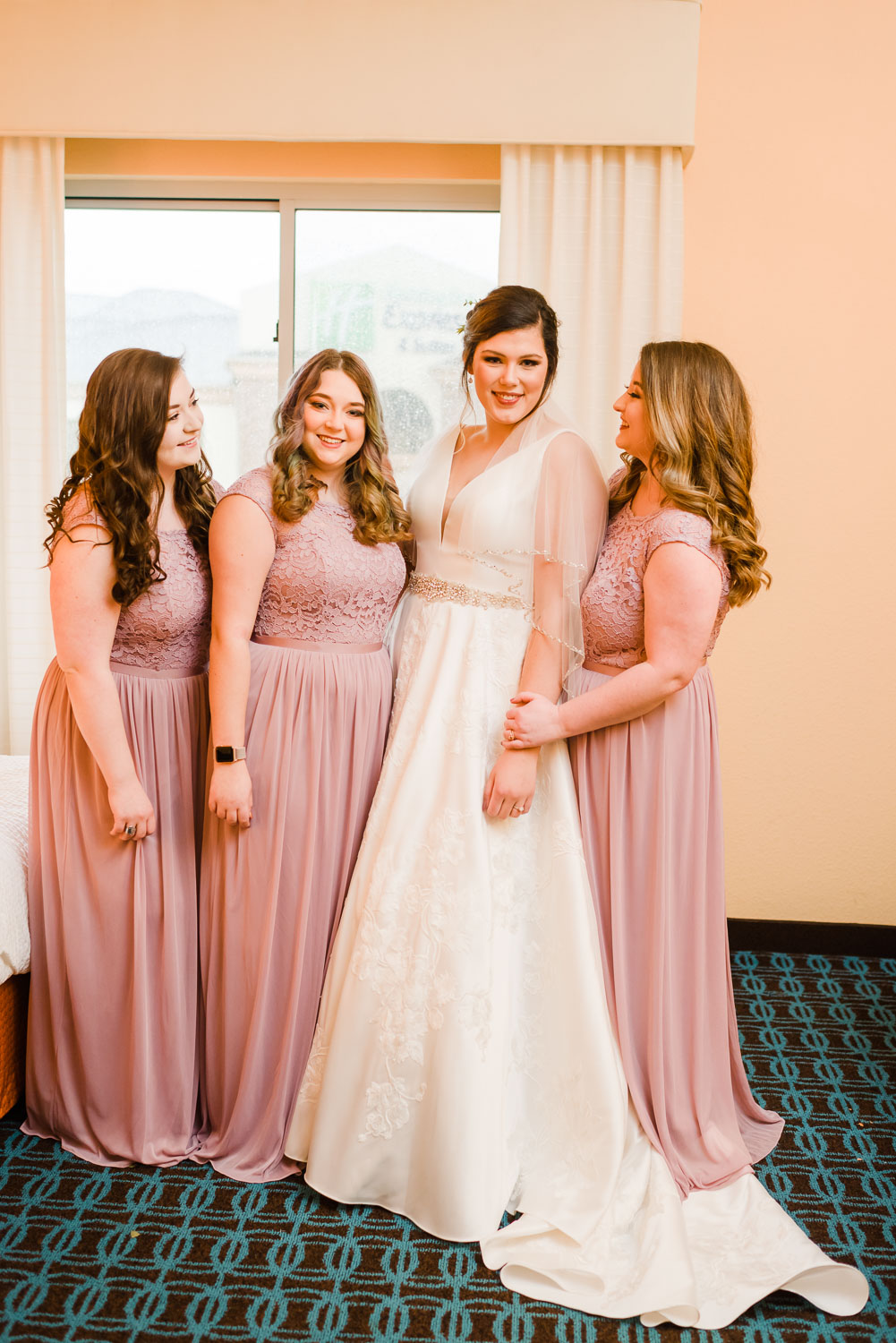 bride and bridesmaids inside a hotel room