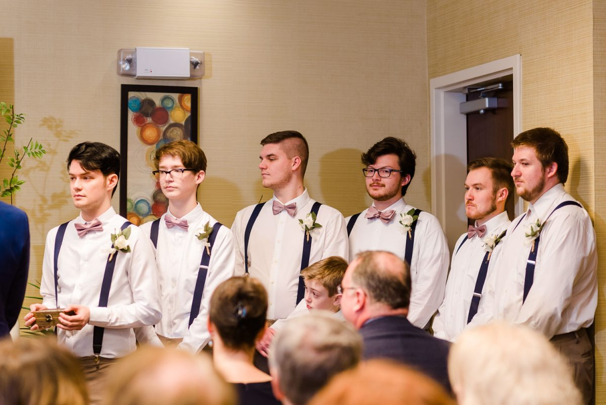 groomsmen standing at indoor wedding ceremony