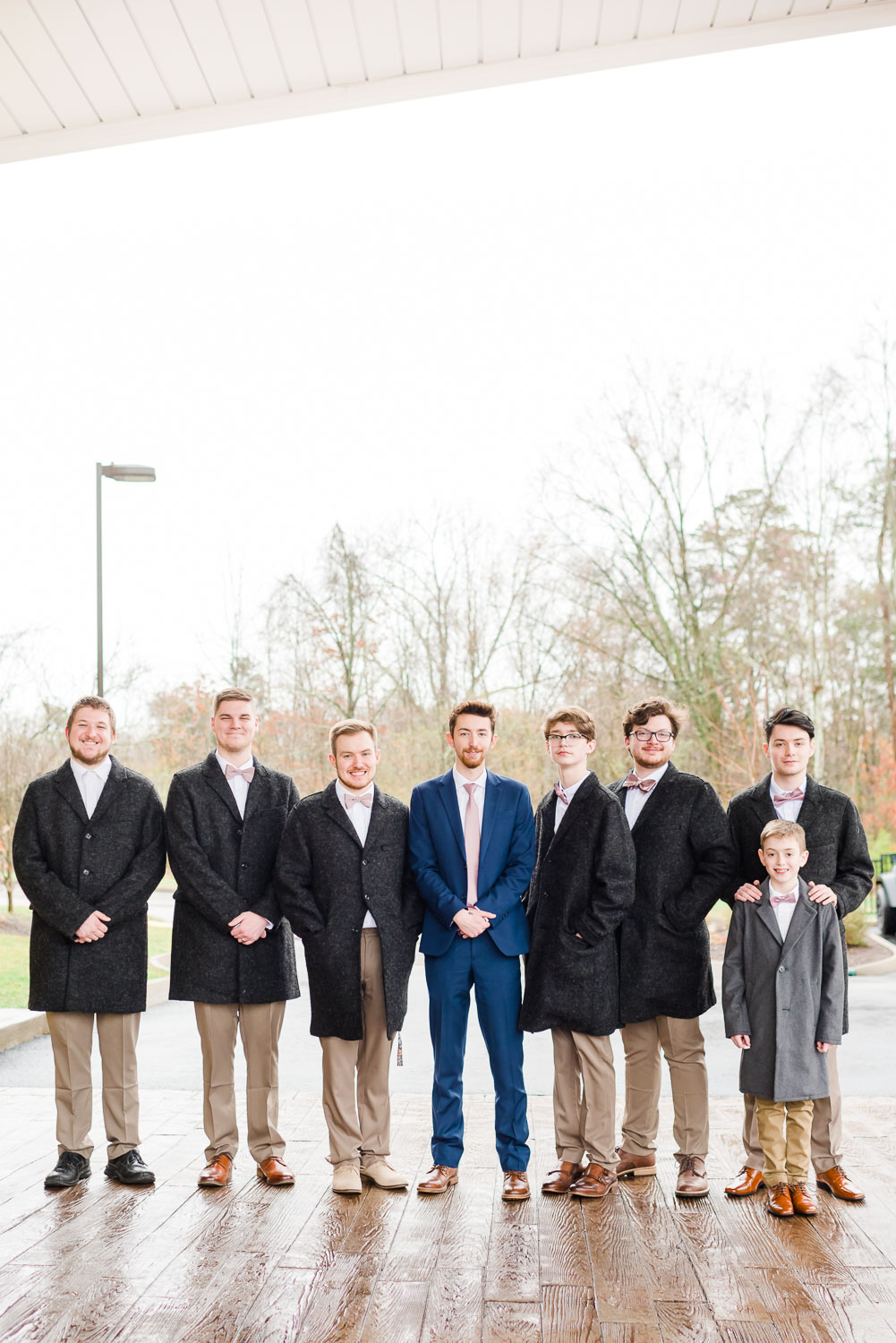 guys in gray jackets and groom in navy blue suit