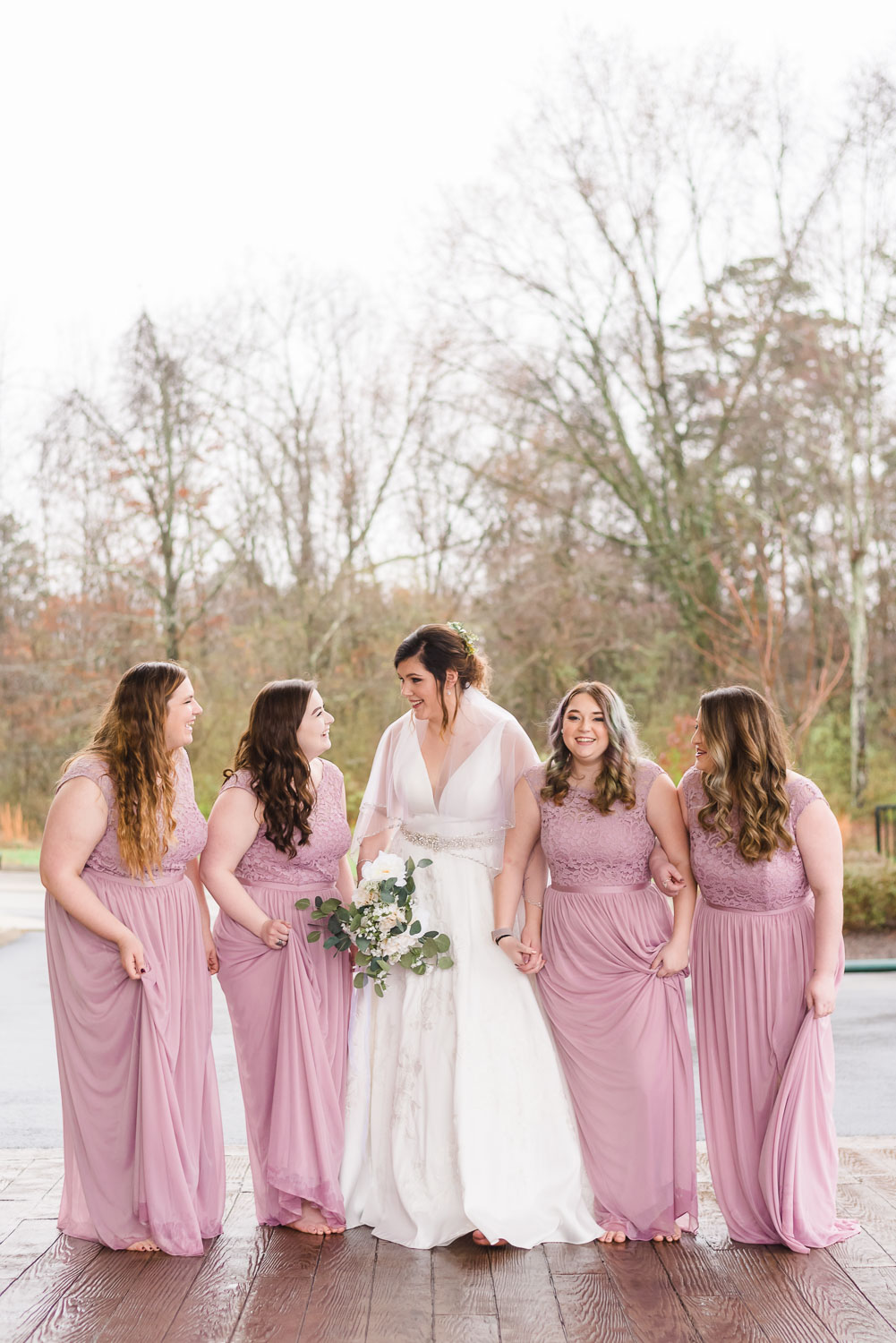 bride and bridesmaids outside in rain in february.