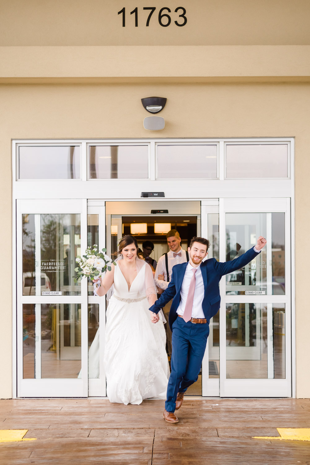 bride and groom running out of the door at the Fairfield Inn on Campbell station rd in Knoxville