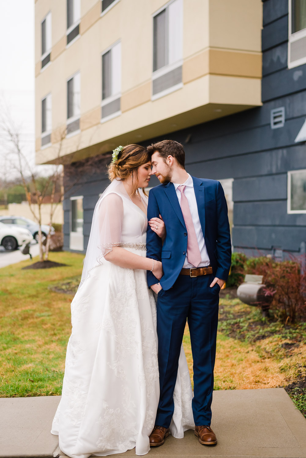 groom in blue suite and bride outside of hotel on their wedding day