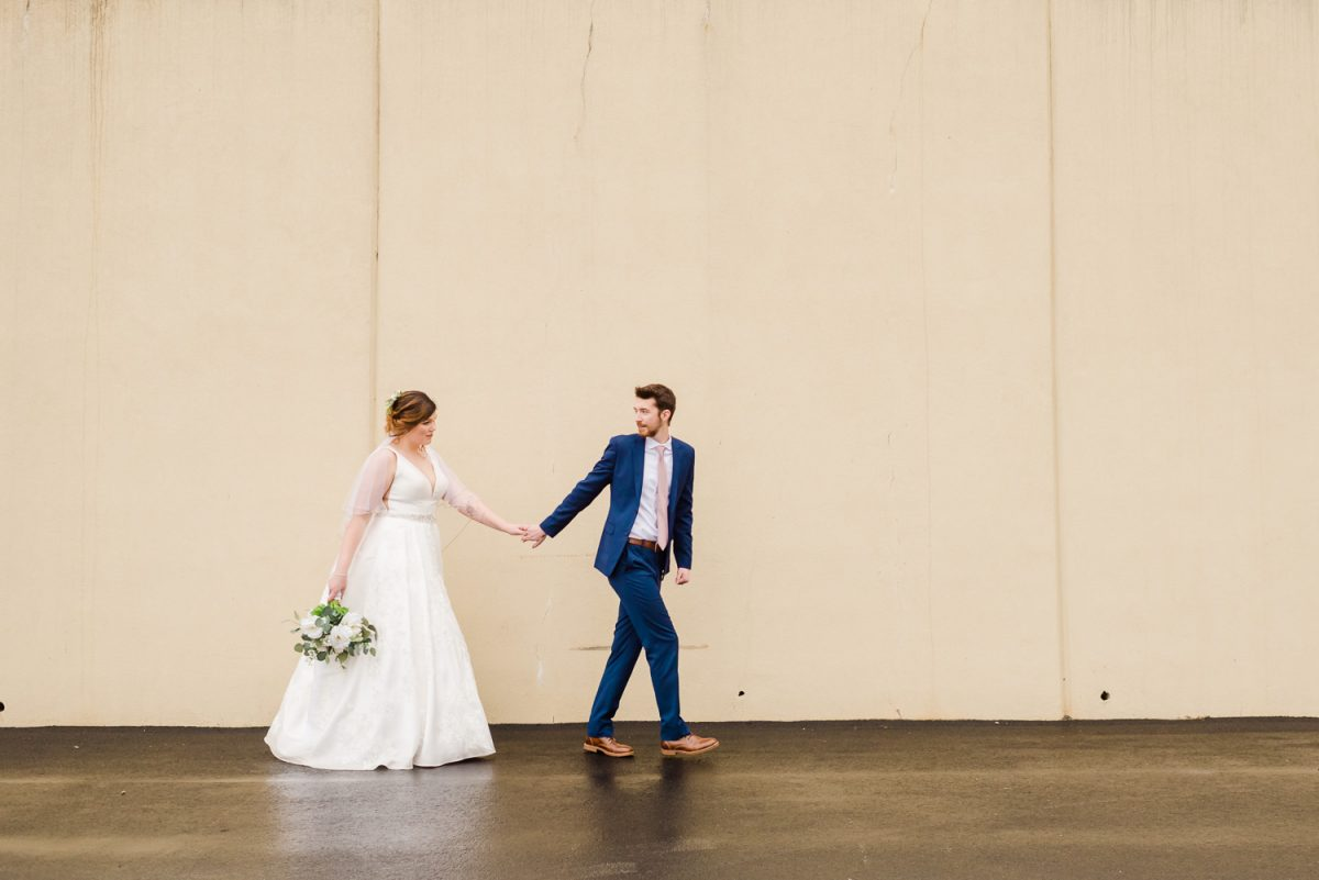 wedding couple walking wearing blue suite and white wedding dress
