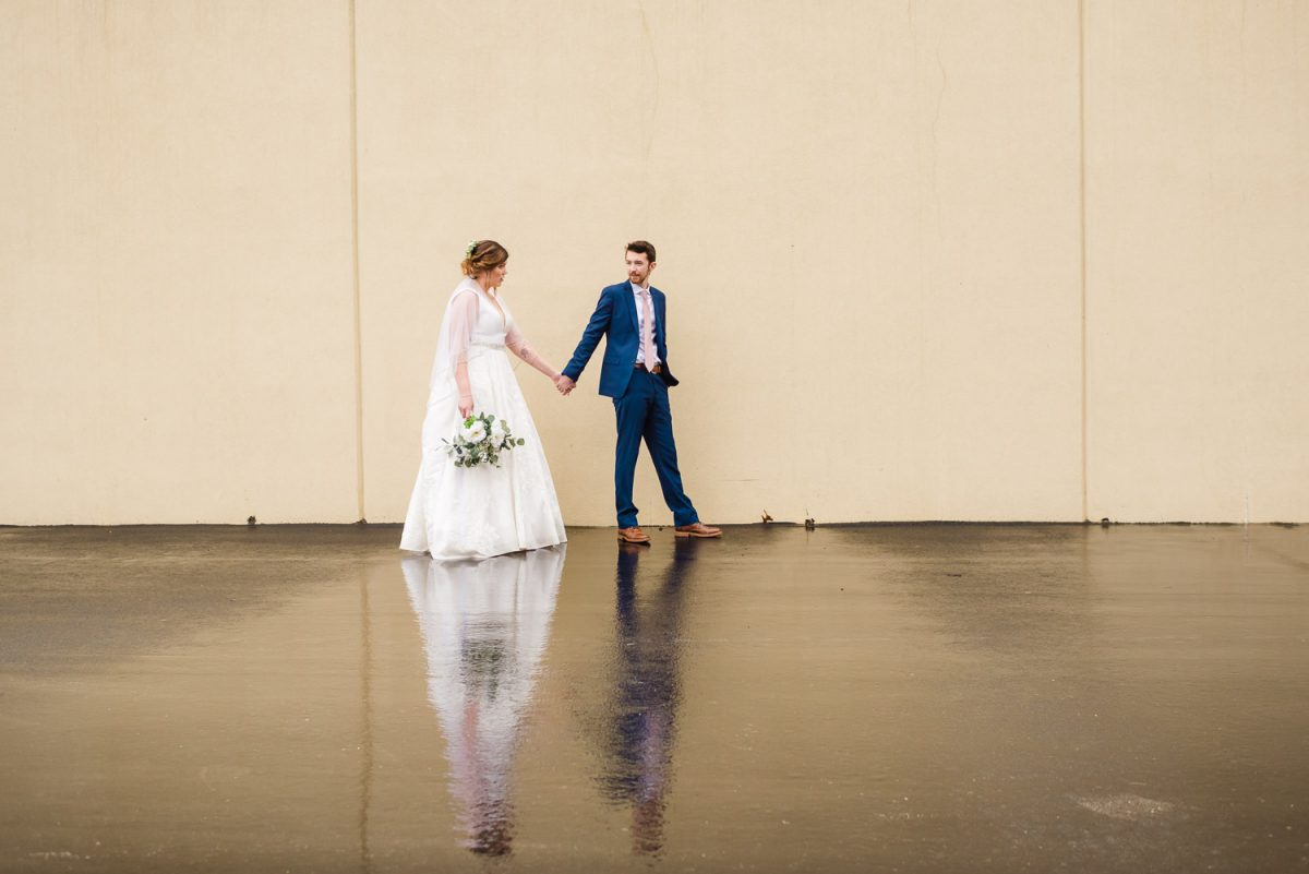 wedding couple walking across wet parking lot behind Fairfield inn in knoxville