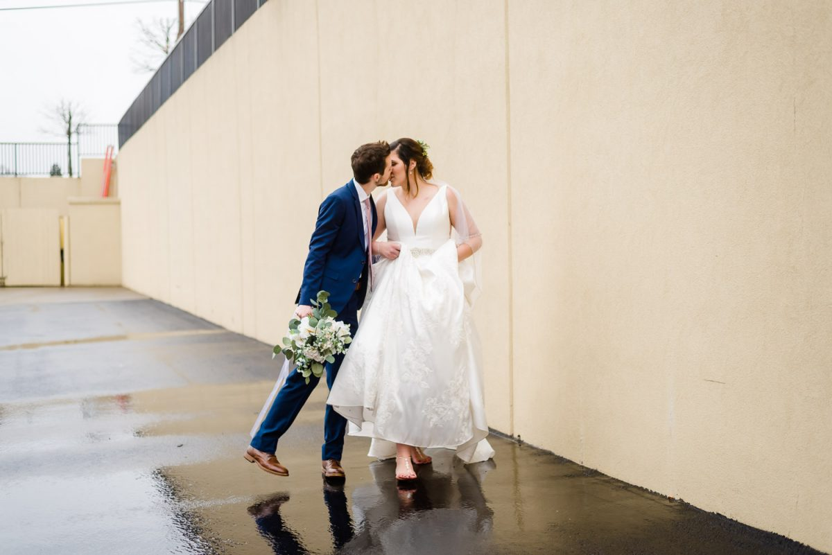 groom leaning in for a kiss with his bride in the rain