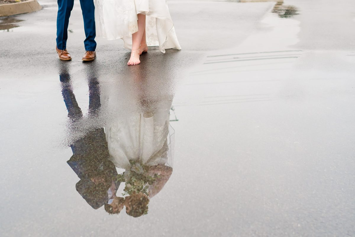 reflection of wedding couple walking in the rain