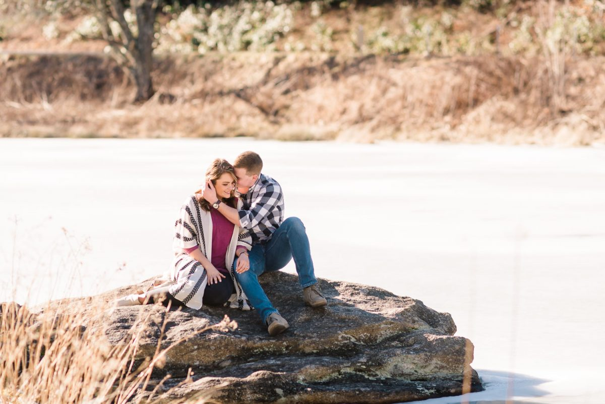 couple sitting on a rock at the edge of a ice covered pond at Max Patch in NC