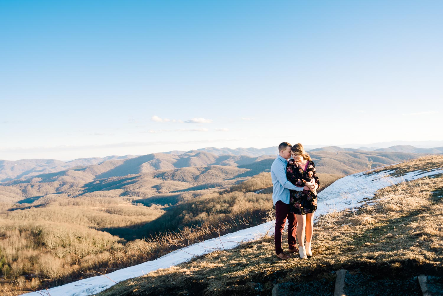 a couple on top of Max Patch wearing a short black floral dress and the guy wearing maroon pants and a blue button down