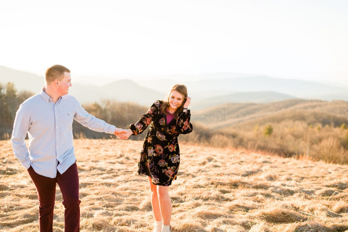 couple holding hands walking up trail to Max patch in the winter in spring like outfits and dress shoes