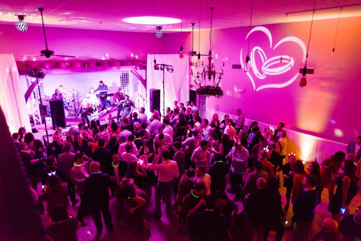 interior of the Venue Chattanooga bathed in hot pink uplighting for a full crowd dancing to a band