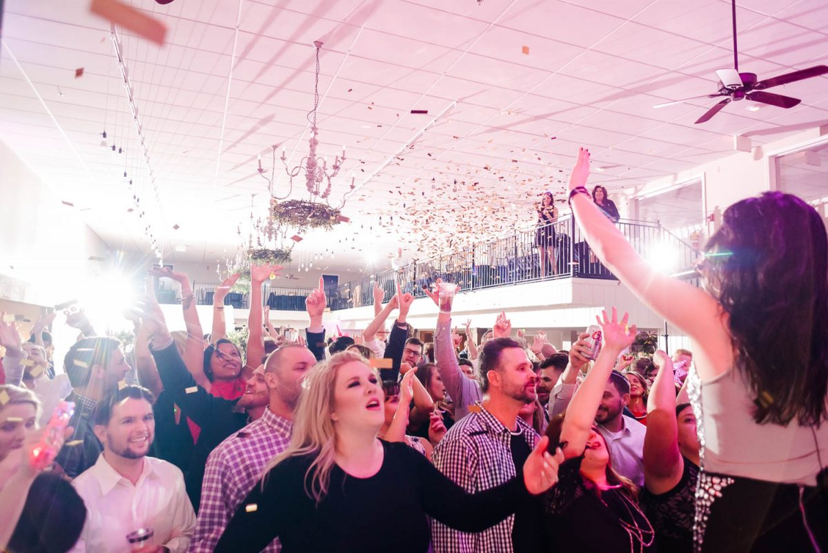 dancing guests with gold confetti falling on them and pink uplighting from the 12 South Band in Chattanooga