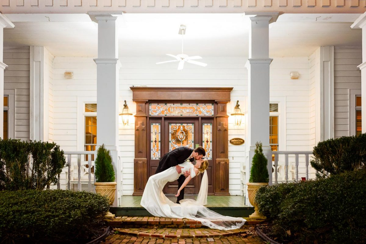 groom dipping his bride waay back for a kiss on the porch at Whitestone Inn in Kingston TN.